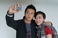 Two young lovers are taking a picture with a mobile phone