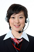 a smelling woman in black business suit wearing an earphone