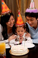 A family is celebrating birthday happily