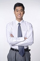 A business man stands and smiles with his arms crossed
