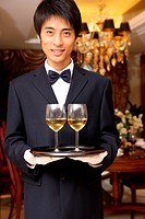A waiter holding two wineglasses
