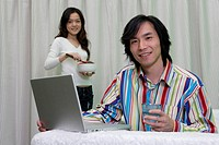 A young couple before a laptop