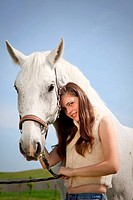 portraite of attractive girl with horse. outdoor shot