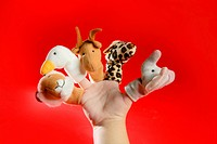 Finger puppets on a toddler hand over red