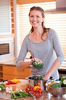 Smiling young woman putting broccoli into pot