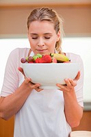 Portrait of a young woman smelling a fruit basket in her kitchen