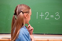 Little schoolgirl thinking while looking at the blackboard