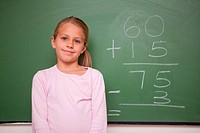 Girl standing up in front a blackboard