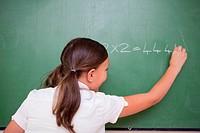 Schoolgirl writing numbers on a blackboard