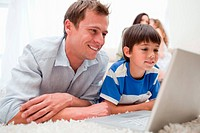 Son and father using laptop together on the carpet