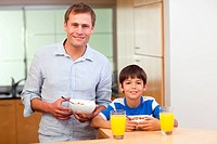 Father and son having cereals and orange juice together