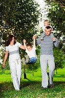Quick family with small children runs on a lawn