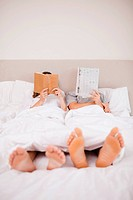 Portrait of playful couple reading in their bedroom
