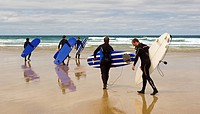 England, Cornwall, Newquay. A group of surfers with their surfboards making their way across Fistral Beach out to sea.