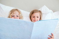 Siblings reading bedtime story together