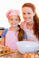 Smiling mother and daughter with ingredients for cookies