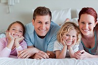 Family lying on the bed together