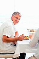 Side view of smiling mature man having dinner