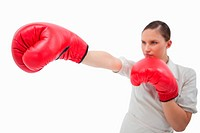Businesswoman punching something with boxing gloves against a white background