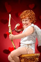 Laughing little boy in an image of the cupid does a shot