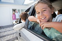 Smiling girl leaning out of car window in grandparents' driveway