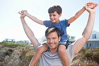 Father carrying son on shoulders with arms outstretched