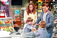 Happy family with children in grocery shop
