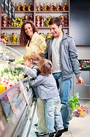 The family with children chooses products in shop