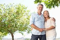 Portrait of smiling senior couple hugging under trees
