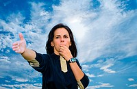 Woman blowing whistle against blue sky