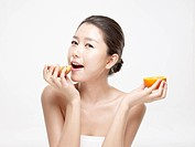Close_up portrait of young woman holding orange and apple slice