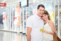 Beautiful couple in the store with credit card