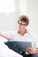 Young attractive man with laptop on sofa