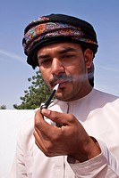 MAN IN THE TRADITIONAL DRESS DISHDASHA SMOKING AN OMANI PIPE, ROAD TO WAHIBA SANDS DESERT, SULTANATE OF OMAN, MIDDLE EAST