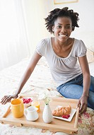 Black woman having breakfast in bed