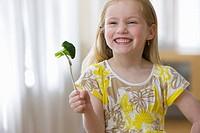 Grinning girl holding broccoli on fork