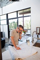Caucasian man reviewing blueprints and talking on cell phone