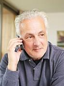 Germany, Munich, Senior man talking on mobile phone