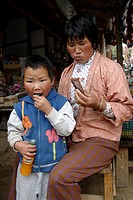 Mother and son eating something at a marketing shed, Bhutan