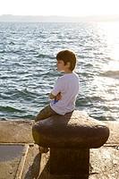 Boy contemplating sea on harbur at sunset