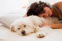 Woman relaxing with dog in bed