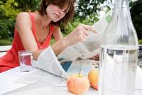 Woman reading newspaper in backyard