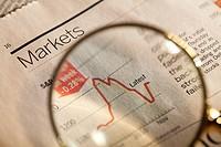 Magnifying glass enlarging stock market chart