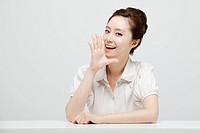 Asian Businesswoman Shouting With Her Hand Around Her Mouth