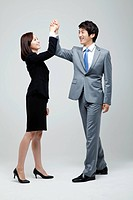 Asian Businessman And Businesswoman Joining Hands