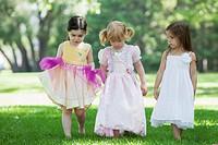 Three girls 3_4 in costumes walking on grass