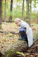 Boy 5_6 in costume kneeling on log in forest