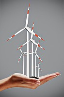 Young woman´s hands with wind turbines