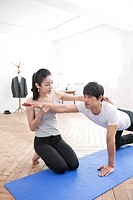 Female Instructor Helping Woman With Pose