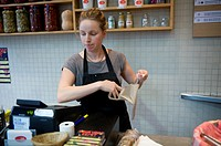 Amsterdam, Netherlands. A young woman is wrapping up a lunch-order for a customer, meanwhile punching in the cash-register.